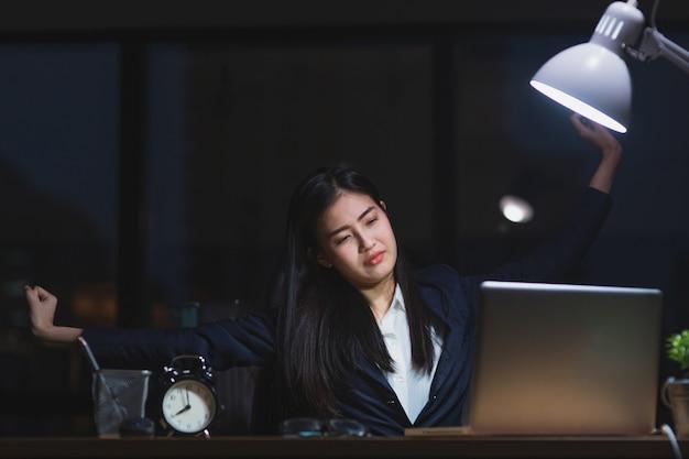 Menina asiática da secretária que trabalha tarde que senta-se na mesa que sente sonolento no escritório na noite.