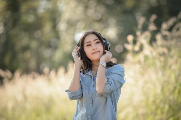 Menina asiática das mulheres com fones de ouvido que escuta música de bluetooth digitas no parque e no fundo de bokeh da grama
