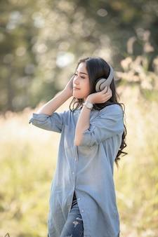 Menina asiática das mulheres com fones de ouvido que escuta música digital de bluetooth no parque