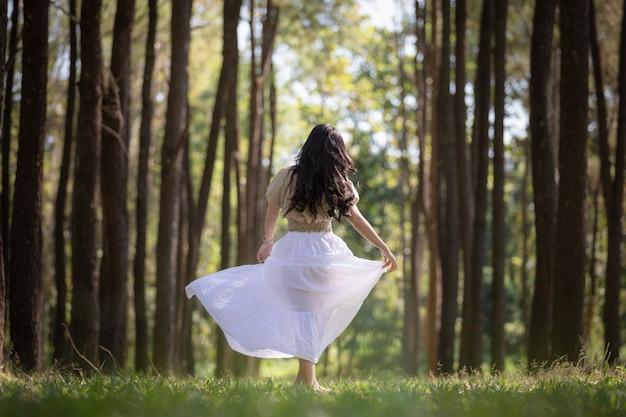 Menina asiática das mulheres que anda no conceito da viagem das férias de verão da floresta do pinho