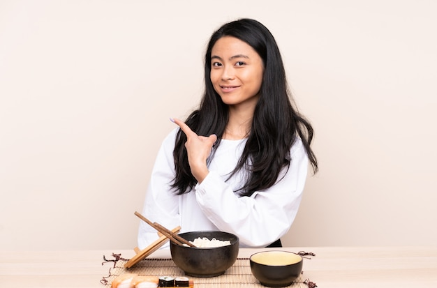 Menina asiática de adolescente comendo comida asiática isolada na parede bege, apontando para o lado para apresentar um produto