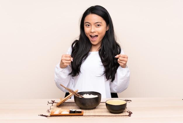 Menina asiática de adolescente comendo comida asiática isolada na parede bege, comemorando uma vitória na posição de vencedor