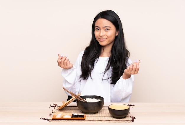 Menina asiática de adolescente comendo comida asiática na parede bege, fazendo dinheiro gesto