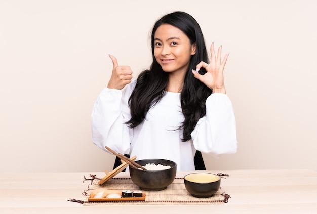 Menina asiática de adolescente comendo comida asiática na parede bege mostrando sinal ok e polegar para cima gesto