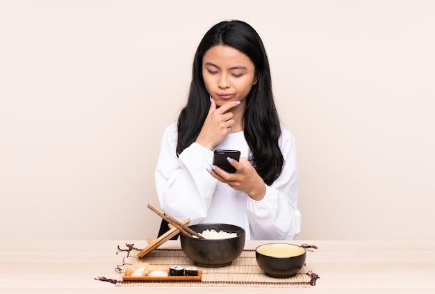 Menina asiática de adolescente comendo comida asiática na parede bege pensando e enviando uma mensagem