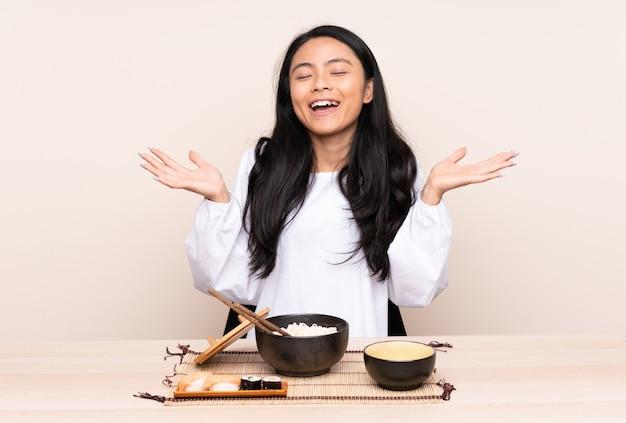 Menina asiática de adolescente comendo comida asiática na parede bege sorrindo muito