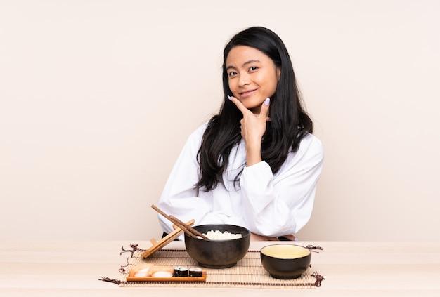 Menina asiática de adolescente comendo comida asiática na parede bege sorrindo