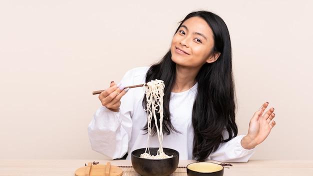 Menina asiática de adolescente comendo comida asiática na parede bege