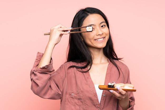 Menina asiática de adolescente comendo sushi isolado em fundo rosa