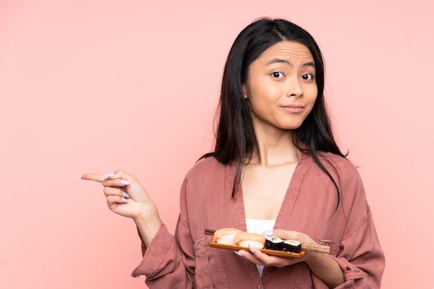 Menina asiática de adolescente comendo sushi isolado na parede rosa, apontando para as laterais tendo dúvidas