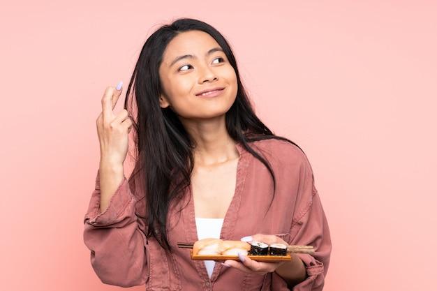 Menina asiática de adolescente comendo sushi isolado na parede rosa com cruzamento de dedos