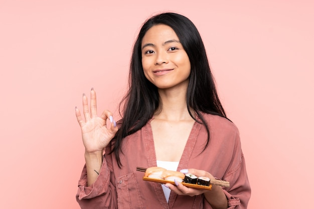 Menina asiática de adolescente comendo sushi isolado na parede rosa, mostrando um sinal de ok com os dedos