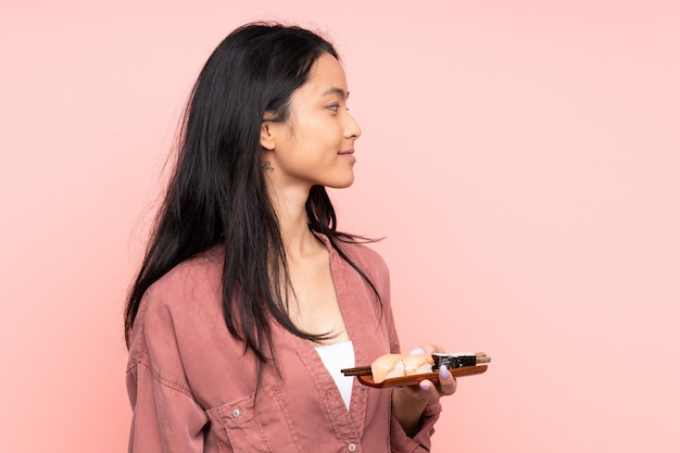 Menina asiática de adolescente comendo sushi isolado na parede rosa, olhando para o lado