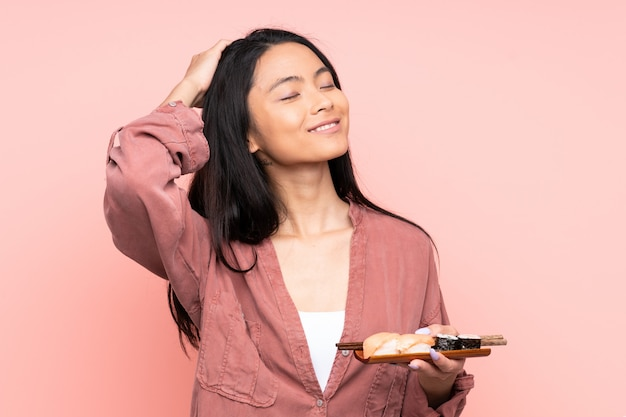 Menina asiática de adolescente comendo sushi isolado na parede rosa rindo