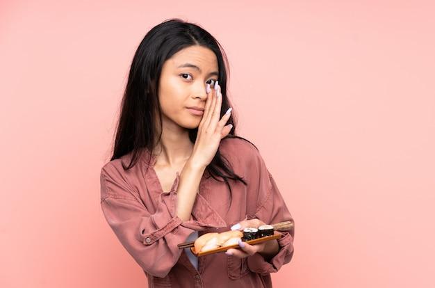 Menina asiática de adolescente comendo sushi isolado na parede rosa sussurrando algo