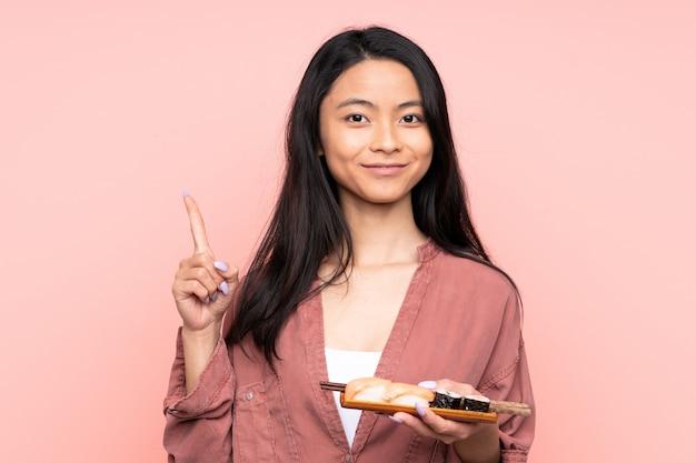 Menina asiática de adolescente comendo sushi isolado no fundo rosa, apontando com o dedo indicador uma ótima idéia