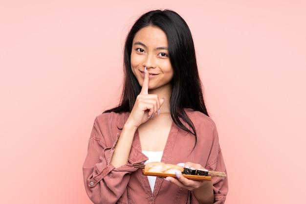 Menina asiática de adolescente comendo sushi isolado no fundo rosa, fazendo o gesto de silêncio