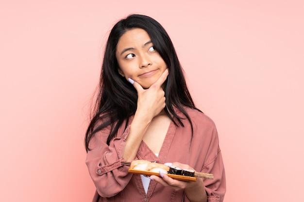 Menina asiática de adolescente comendo sushi isolado no fundo rosa, pensando uma idéia