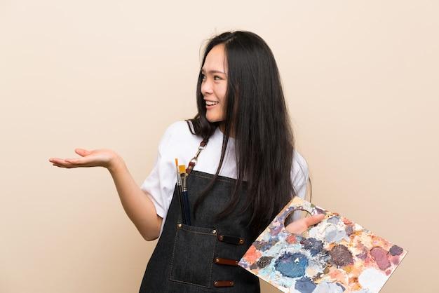 Menina asiática de adolescente pintor com expressão facial de surpresa