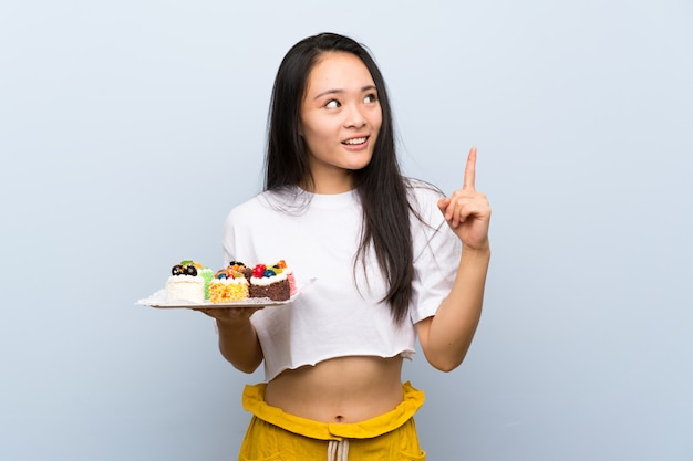 Menina asiática de adolescente segurando muitos mini bolos diferentes com a intenção de realizar a solução enquanto levanta um dedo