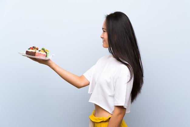 Menina asiática de adolescente segurando muitos mini bolos diferentes com expressão feliz