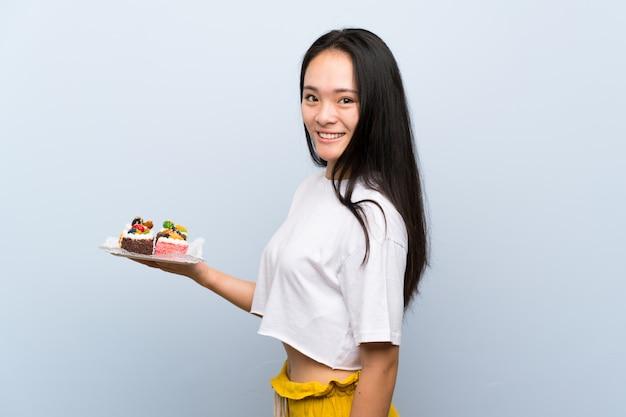 Menina asiática de adolescente segurando muitos mini bolos diferentes, sorrindo muito