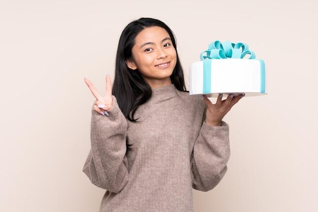 Menina asiática de adolescente segurando um bolo grande isolado em bege
