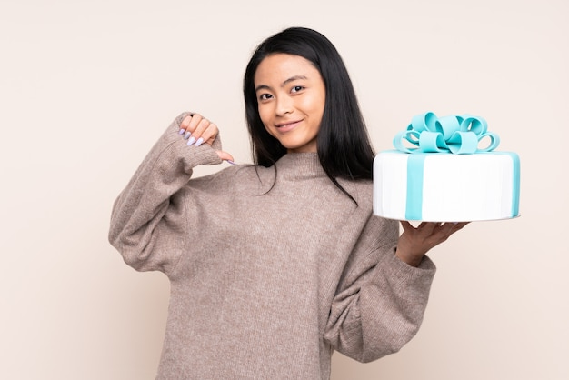 Menina asiática de adolescente segurando um bolo grande isolado na parede bege, orgulhoso e satisfeito