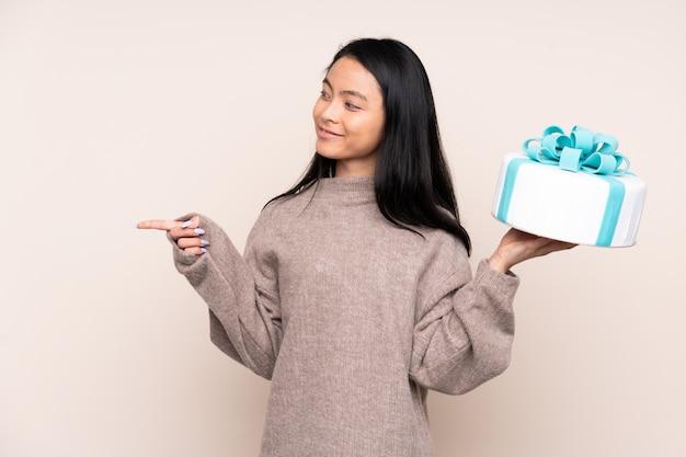 Menina asiática de adolescente segurando um bolo grande na parede bege, apontando para o lado para apresentar um produto