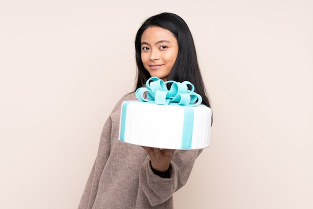 Menina asiática de adolescente segurando um bolo grande na parede bege com expressão feliz