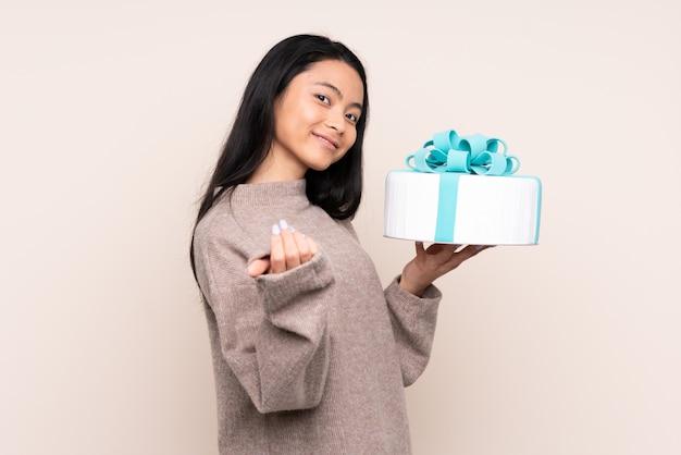 Menina asiática de adolescente segurando um bolo grande na parede bege, convidando para vir com a mão