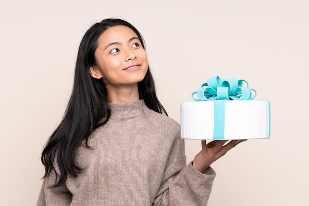 Menina asiática de adolescente segurando um bolo grande na parede bege, olhando para cima enquanto sorrindo