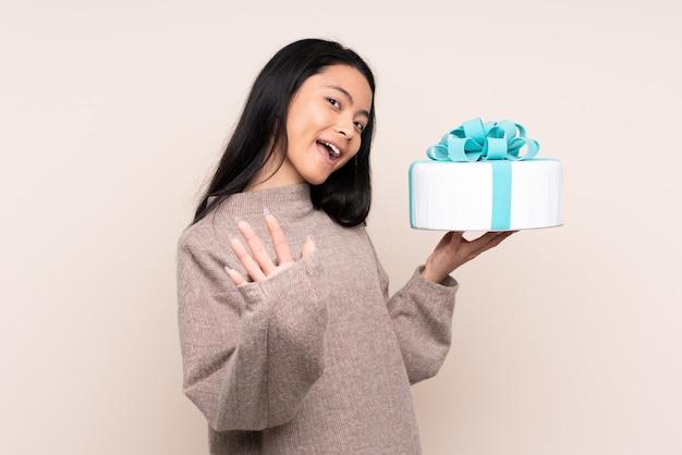 Menina asiática de adolescente segurando um bolo grande na parede bege saudando com a mão com expressão feliz