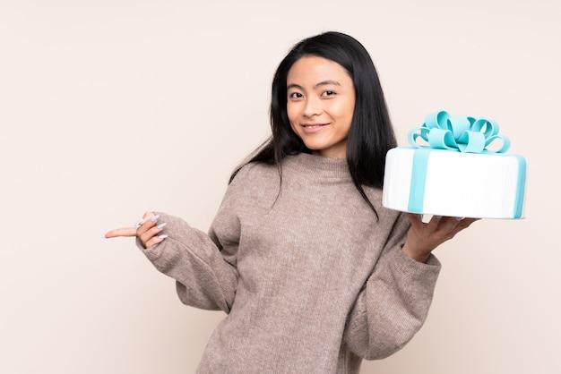 Menina asiática de adolescente segurando um bolo grande na parede bege surpreendeu e apontando o dedo para o lado