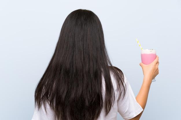 Menina asiática de adolescente segurando um milk-shake de morango em posição traseira