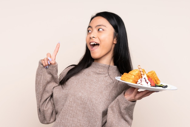 Menina asiática de adolescente segurando waffles isolados em bege