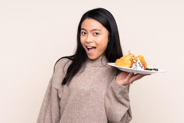 Menina asiática de adolescente segurando waffles na parede bege com surpresa e expressão facial chocada