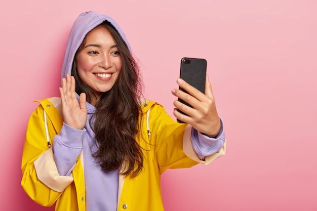 Menina asiática de aspecto agradável acena a palma da mão e diz olá para a câmera do smartphone moderno, faz videochamada, tem longos cabelos escuros, usa moletom roxo e capa de chuva amarela, posa dentro de casa.