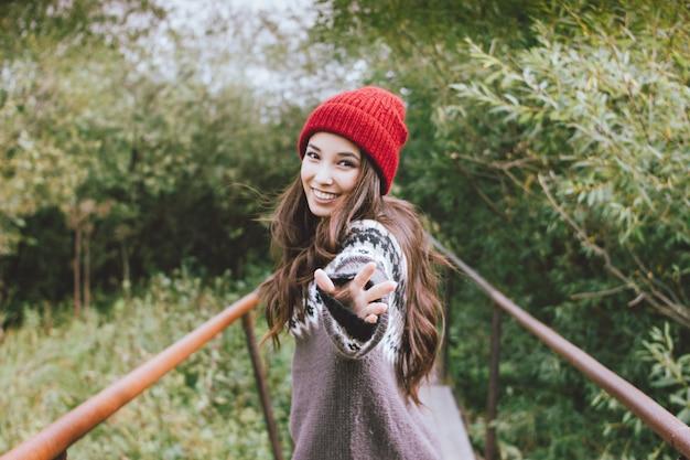Menina asiática de cabelo comprido despreocupado bonito de chapéu vermelho e camisola nórdica de malha no parque natural de outono, estilo de vida de aventura de viagem
