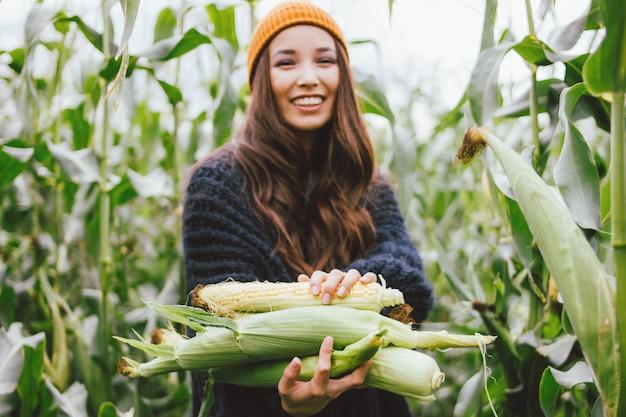 Menina asiática de cabelo comprido despreocupado bonito no chapéu amarelo e camisola de malha segurando espigas de milho no campo de outono. foco seletivo nas mãos. sensibilidade ao conceito de natureza