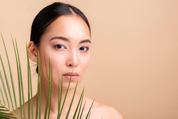 Menina asiática de close-up posando com folhas