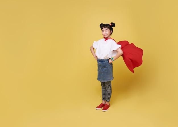 Menina asiática de criança joga super-herói em um tiro de estúdio de fundo amarelo. conceito de herói de poder feminino.