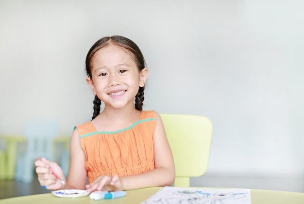 Menina asiática de desenho e pintura com água