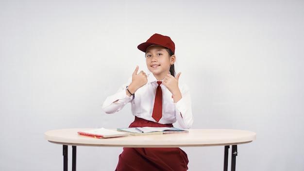 Menina asiática de escola primária estudando adequadamente isolada no fundo branco
