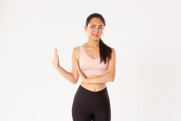 Menina asiática de fitness descontente e sem graça, mostrando o bloco com a mão e olhando para a esquerda com nojo, expressar aversão e rejeitar algo ruim.