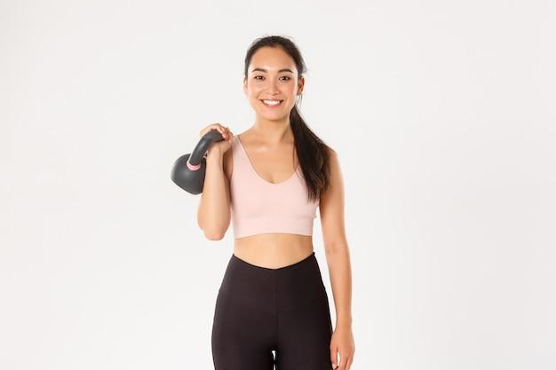 Menina asiática de fitness forte e magra sorridente, atleta segurando o kettlebell e parecendo despreocupada, ganhando músculos na academia, em pé
