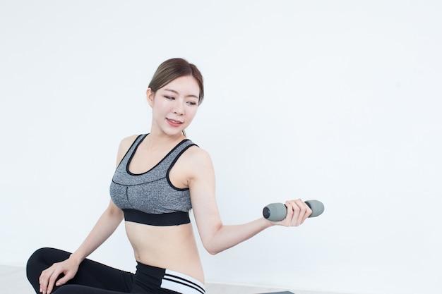 Menina asiática de fitness jovem levantando halteres, treino no conceito de quarto, fitness, treinamento e estilo de vida