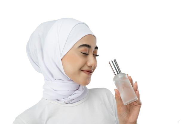 Menina asiática de hijab sorridente usando um vestido branco quando fecha os olhos, segurando um frasco de sér ...