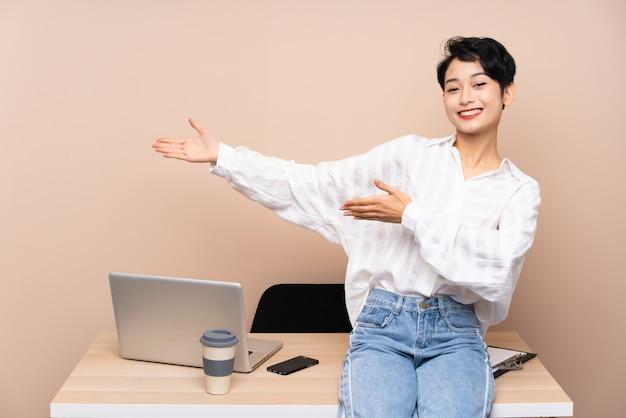 Menina asiática de negócios jovem em seu local de trabalho, estendendo as mãos para o lado para convidar para vir