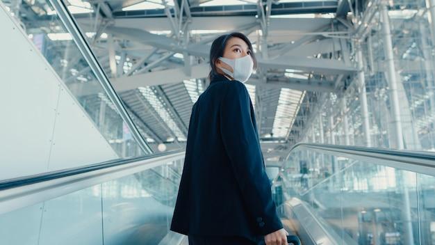 Menina asiática de negócios usando máscara e arrastando bagagem na escada rolante